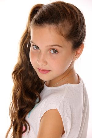 かわいい十代の少女の肖像画クローズアップ。白い背景に黒髪と魅力的な顔を持つ愛らしい十代。子供の夏のファッションのイメージ。 写真素材 - 93322466