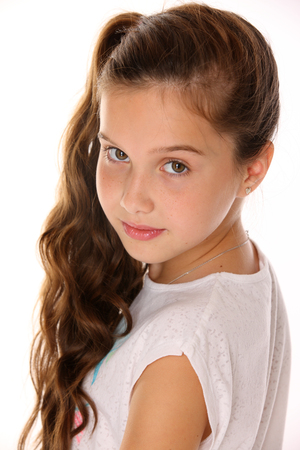 Portrait of a pretty young teenage girl close-up. Adorable preteen with dark hair and charming face on a white background. The image of childrens summer fashion.