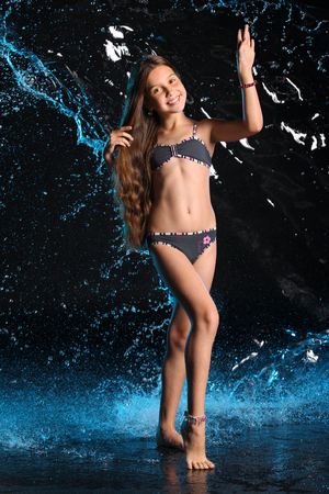 Attractive happy young teenage girl posing in a dark bikini. The child with long chic hair and a beautiful slender body smiles charmingly. Lovely pre-teen female dances barefoot in swimsuit.