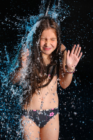 Conceptual photo: negative, stress, trouble, fright. The water flow falls on a gentle little slender child girl in a bikini. Young female teenager in a falling stream of water.