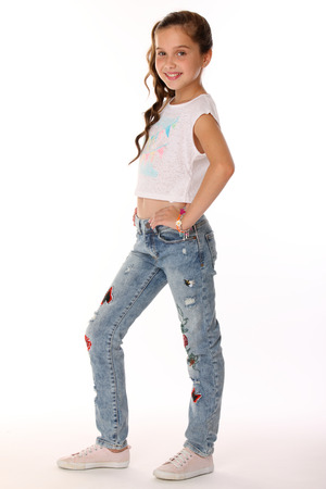 Portrait of happy slender cheerful teenage girl in full body. The child elegantly poses and smiles. Young fashionista in blue jeans and with a bare belly.