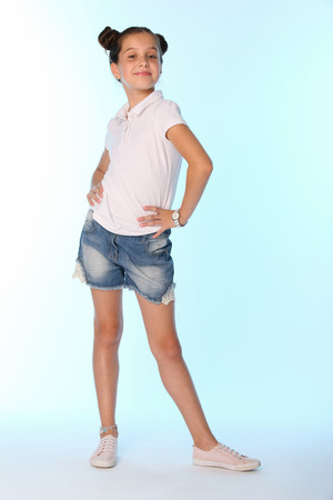 Happy slender cheerful teenage girl in full growth. The child gracefully poses and has fun. The young fashionista in denim shorts with bare legs. Фото со стока