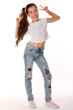 Portrait of happy slender cheerful teenage girl in full body. The child elegantly poses makes funny faces and shows her tongue. Young fashionista in blue jeans and with a bare belly.