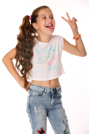 Portrait of happy slender cheerful teenage girl. The child elegantly poses makes funny faces and shows her tongue. Young fashionista in blue jeans and with a bare belly.
