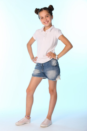Happy slender cheerful teenage girl in full growth. The child gracefully poses and has fun. The young fashionista in denim shorts with bare legs. Stock Photo