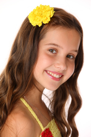 Close-up portrait of a beautiful charming happy young teenage girl in a yellow top and flower-pin. Adorable brunette child with chic long hair playfully looks and smiles. Stockfoto