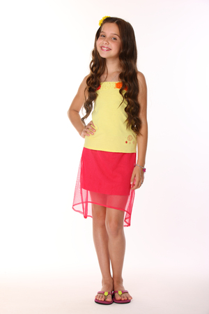 Pretty brunette slender child with chic long hair is stands full-length in a red skirt with bare legs. Beautiful charming happy young teenage girl smiles. Stockfoto