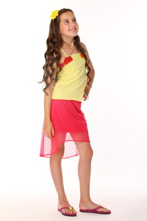 Pretty brunette slender child with chic long hair is stands full-length in a red skirt with bare legs. Beautiful charming happy young teenage girl smiles. Фото со стока
