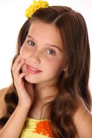 Retrato de primer plano de una hermosa encantadora feliz joven adolescente en un top amarillo y flor-pin. Bonita niña morena con elegante cabello largo se ve de cerca y sonríe levemente.