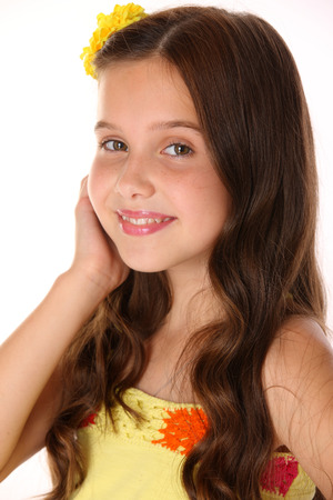 Close-up portrait of a beautiful charming happy young teenage girl in a yellow top and flower-pin. Pretty brunette child with chic long hair playfully looks and smiles.