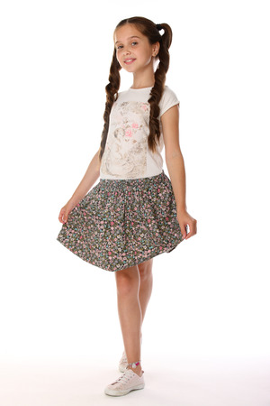 A little girl 12 years old posing in summer clothes. Charming pretty slender young teenager is in a skirt with bare legs. Beautiful brunette child is standing at full length and smiles slightly. Reklamní fotografie - 97763782