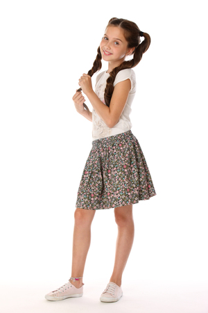 A little girl 12 years old posing in summer clothes. Charming pretty slender young teenager is in a skirt with bare legs. Beautiful brunette child is standing at full length and smiles slightly. Reklamní fotografie - 97763723