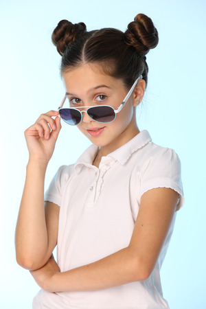 Portrait of a charming pretty stylish young teenage schoolgirl. Beautiful brunette child is looking cool with sunglasses. The little girl 12 years old in a white blouse.