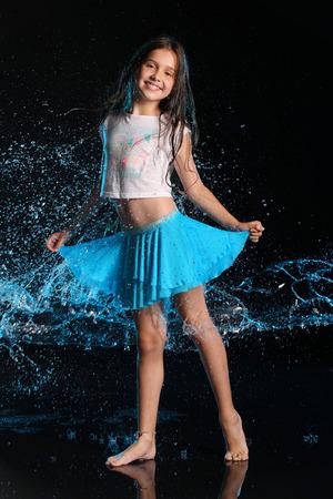 Charmant slank kind dat zich op volledig lichaam en glimlach bevindt. Vrij jong mooi meisje met blote benen in natte kleren en rok. Aantrekkelijke gelukkige tiener in spatten van water.