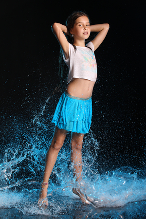 Charming slender child standing at full body on tiptoe. Pretty young beautiful girl with bare legs in wet clothes and skirt. Attractive yound teenager in splashes of water. Stok Fotoğraf - 98180080