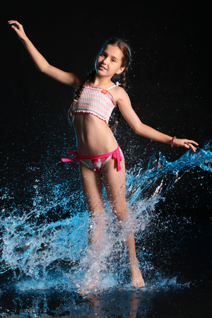Charming slender child standing at full body on tiptoe. Pretty young beautiful girl with bare legs elegantly posing in wet bright bikini. Attractive young teenager in splashes of water.