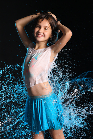 Portrait of a charming slender child standing with wet body and smile. Pretty young beautiful girl with bare belly in wet clothes and skirt. Attractive happy teenager in splashes of water. Stok Fotoğraf