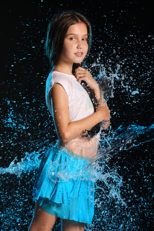 Portrait of a charming child standing with wet slender body. Pretty young beautiful girl with bare belly in wet clothes and skirt. Attractive young teenager in splashes of water. Foto de archivo