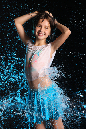 Portrait of a charming slender child standing with wet body and smile. Pretty young beautiful girl with bare belly in wet clothes and skirt. Attractive happy teenager in splashes of water. Foto de archivo