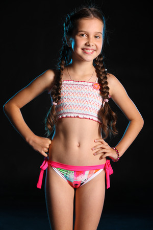 Portrait of a charming child standing with slender body. Pretty young beautiful girl with bare belly posing in bright bikini. Attractive young teenager smiling and happy. Archivio Fotografico