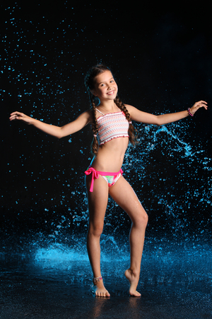 Charming slender child standing at full body on tiptoe and smile. Pretty young beautiful happy girl with bare legs elegantly posing in wet bikini. Attractive young teenager in splashes of water.