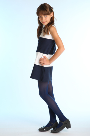 Beautiful girl in a striped dress is standing at full length. Elegant attractive child with a slender body and long legs in blue tights. The young schoolgirl is 9 years old. 版權商用圖片