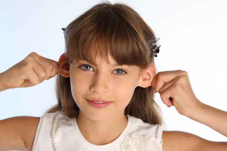 Close-up portrait of a beautiful girl in a white blouse. The cute attractive child pulls her nice ears. The young schoolgirl is 9 years old.
