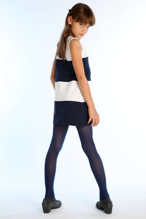 Beautiful girl in a striped dress poses with her back turned. Elegant attractive child with a slender body and long legs in blue tights. The young schoolgirl is 9 years old. Imagens