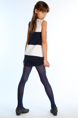 Beautiful girl in a striped dress poses with her back turned. Elegant attractive child with a slender body and long legs in blue tights. The young schoolgirl is 9 years old. Zdjęcie Seryjne