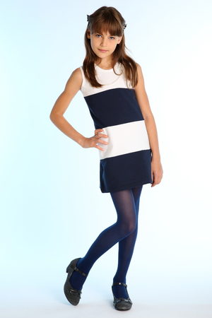 Beautiful girl in a striped dress is standing at full length. Elegant attractive child with a slender body and long legs in blue tights. The young schoolgirl is 9 years old. Stockfoto