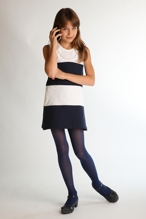 Beautiful girl in a striped dress is standing at full length with a smartphone and smiling. Attractive child with a slender body and long legs in blue tights. The young schoolgirl is 9 years old.