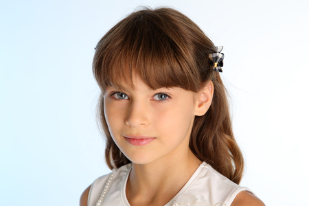 Close-up portrait of a beautiful girl in a white blouse. Pretty attractive child. The young schoolgirl is 9 years old.