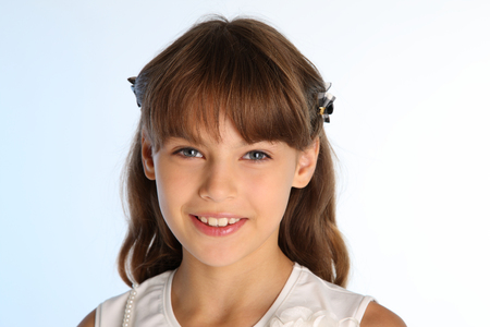Close-up portrait of a beautiful girl in a white blouse. Charming happy attractive child smiling. The young schoolgirl is 9 years old.