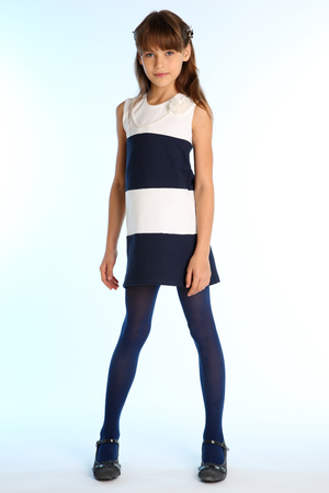 Beautiful girl in a striped dress is standing at full length. Elegant attractive child with a slender body and long legs in blue tights. The young schoolgirl is 9 years old. 스톡 콘텐츠