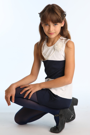 Slender beautiful girl in a striped dress sat on her knee. Pretty happy attractive child in blue tights. The young schoolgirl is 9 years old.