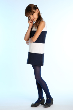 Beautiful girl in a striped dress is standing at full length. Elegant attractive child with a slender body and long legs in blue tights. The young schoolgirl is 9 years old. 免版税图像