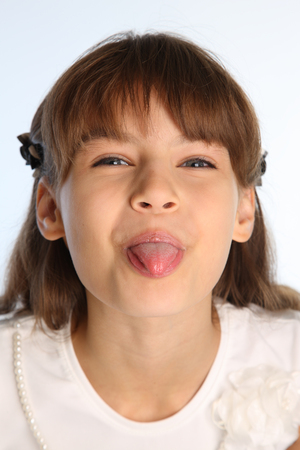 Close-up portrait of a beautiful girl in a white blouse. Cute attractive child teases and shows her pink tongue. The young schoolgirl is 9 years old. Foto de archivo