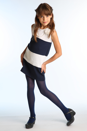 Beautiful girl in a striped dress is standing at full length. Elegant attractive child with a slender body and long legs in blue tights. The young schoolgirl is 9 years old. Zdjęcie Seryjne