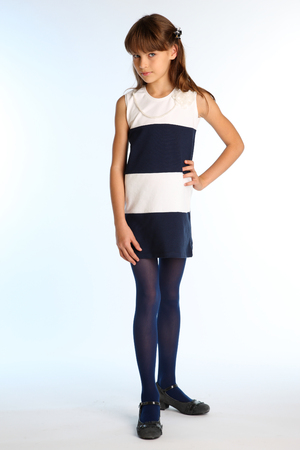 Beautiful girl in a striped dress is standing at full length. Elegant attractive child with a slender body and long legs in blue tights. The young schoolgirl is 9 years old. Stock Photo