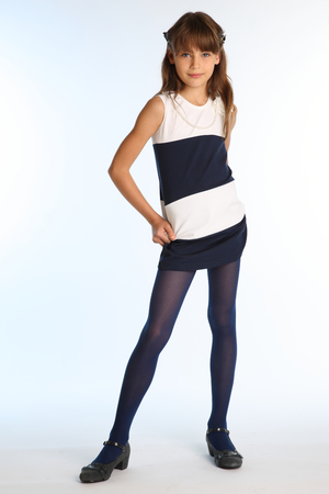 Beautiful girl in a striped dress is standing at full length. Elegant attractive child with a slender body and long legs in blue tights. The young schoolgirl is 9 years old. Imagens