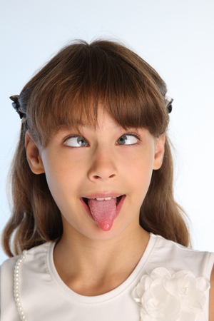 Close-up portrait of a beautiful girl in a white blouse. The cute attractive child teases by pulling her pink tongue and rolling her eyes. The young schoolgirl is 9 years old. Stockfoto