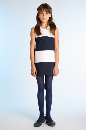 Beautiful girl in a striped dress is standing at full length. Elegant attractive child with a slender body and long legs in blue tights. The young schoolgirl is 9 years old. Foto de archivo