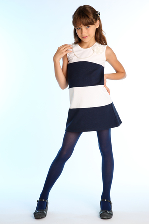 Beautiful girl in a striped dress is standing at full length and smiling. Elegant attractive child with a slender body and long legs in blue tights. The young schoolgirl is 9 years old.