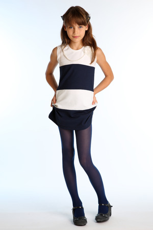 Beautiful girl in a striped dress is standing at full length. Elegant attractive child with a slender body and long legs in blue tights. The young schoolgirl is 9 years old. Banque d'images