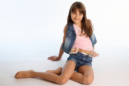 Beautiful girl in a denim shorts is resting on the floor barefoot. Elegant attractive child with a slender body and bare long legs. The young schoolgirl is 9 years old. Imagens