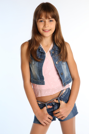 Portrait of a beautiful girl in a denim shorts is standing. Elegant attractive child with a slender body and long legs in pantyhose. The young schoolgirl is 9 years old.