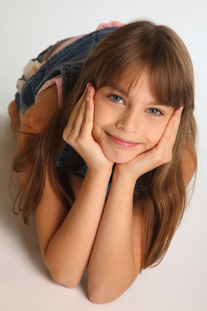 Portrait of a beautiful girl in a denim shorts is resting on the floor. Pretty attractive child with a lovely smiling face. The young schoolgirl is 9 years old. Stock Photo