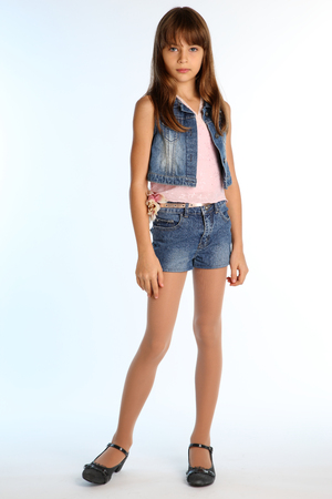 Beautiful girl in a denim shorts is standing at full length. Elegant attractive child with a slender body and long legs in pantyhose. The young schoolgirl is 9 years old. Фото со стока - 100516697
