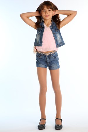 Beautiful girl in a denim shorts is standing at full length. Elegant attractive child with a slender body and long legs in pantyhose. The young schoolgirl is 9 years old.