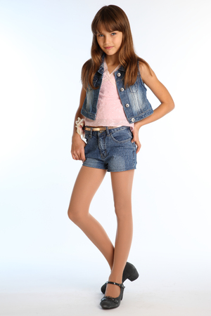 Beautiful girl in a denim shorts is standing at full length. Elegant attractive child with a slender body and long legs in pantyhose. The young schoolgirl is 9 years old. Reklamní fotografie - 100516709